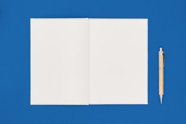 Cuaderno y pluma sobre fondo azul. lista de deseos o concepto de objetivos. vista superior, plano, copia espacio. color de moda del año 2020.