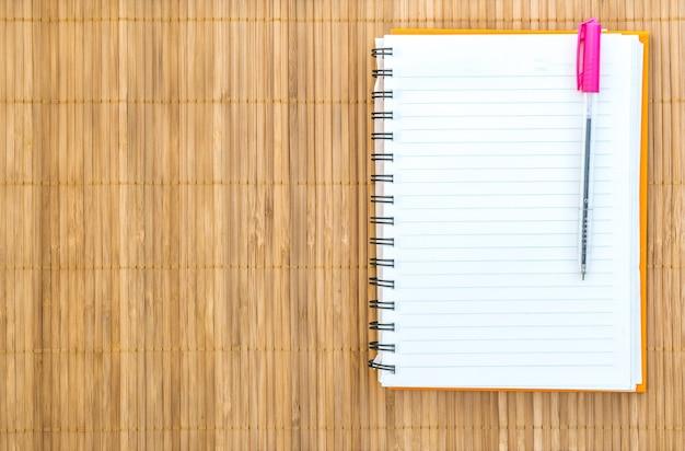 Cuaderno con pluma sobre fondo de madera