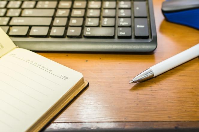 Cuaderno, pluma, teclado y ratón en el escritorio de oficina de madera.