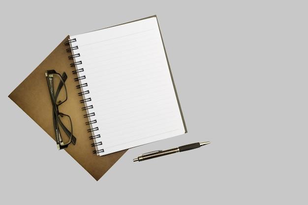 Cuaderno, pluma y vidrios del espacio en blanco de la visión superior en el fondo blanco del escritorio.