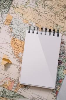 Cuaderno de primer plano y avión de papel en el mapa