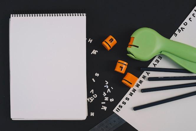 Cuaderno que miente cerca del cortador de la letra