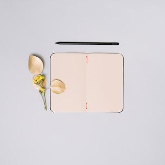 Cuaderno con rama de flores en mesa de luz