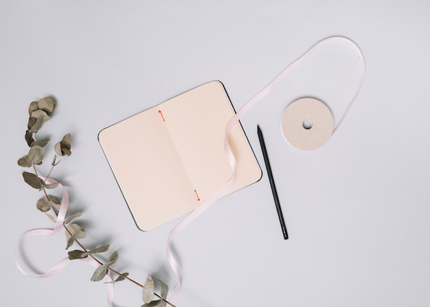 Cuaderno con rama pequeña y cinta en mesa
