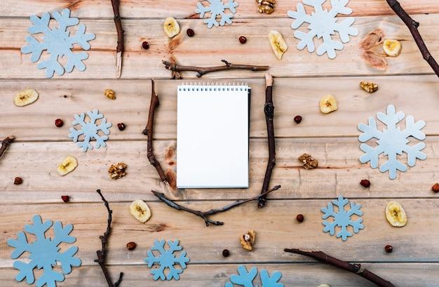 Cuaderno entre ramitas y copos de nieve de papel.