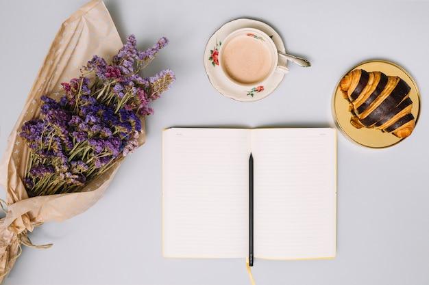 Cuaderno con ramo de flores y croissant.