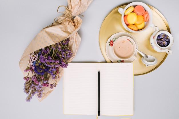 Cuaderno con ramo de flores y galletas en bandeja