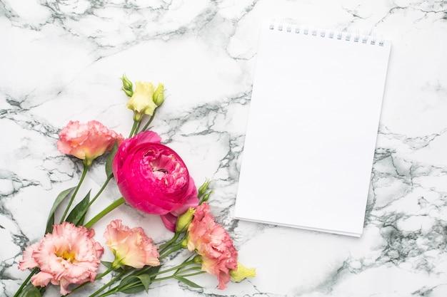 Cuaderno y ramo de flores rosadas sobre fondo de mármol