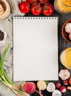 Cuaderno para receta tomate farfalle ajo cebolla mortero pimienta vista superior copia espacio