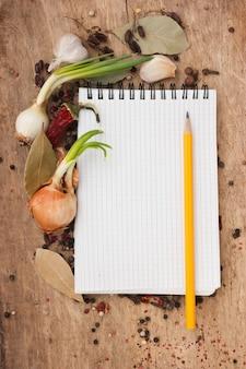 Cuaderno para recetas y especias en una vieja mesa de madera