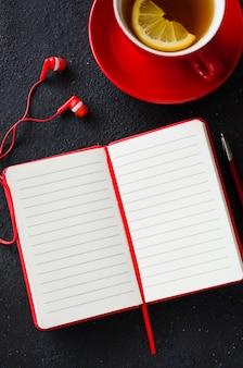 Cuaderno rojo en blanco, computadora portátil, auriculares y taza de té. concepto de negocio o educación.
