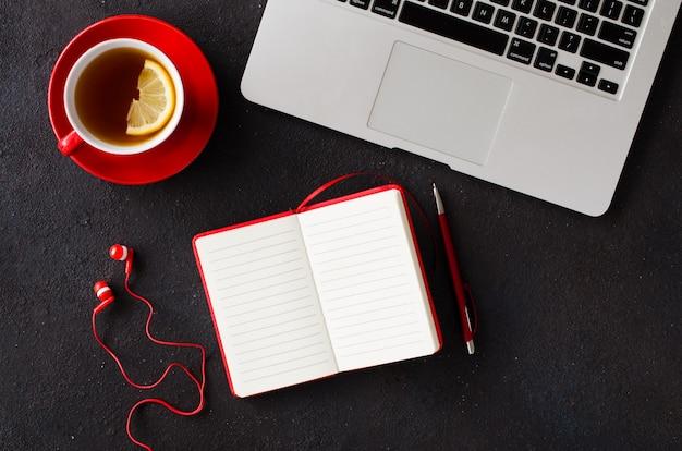 Cuaderno rojo en blanco, computadora portátil, auriculares y taza de té.