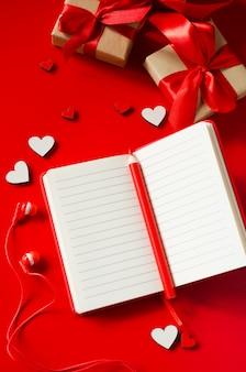 Cuaderno rojo, cajas de regalo, corazones de madera, lápiz y auriculares.