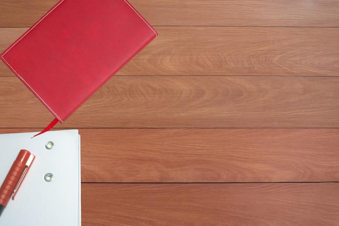 Cuaderno rojo y blanco con lápiz en el piso de madera