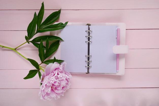 Cuaderno rosa en blanco y flor de peonía rosa sobre fondo de tablero de madera rosa