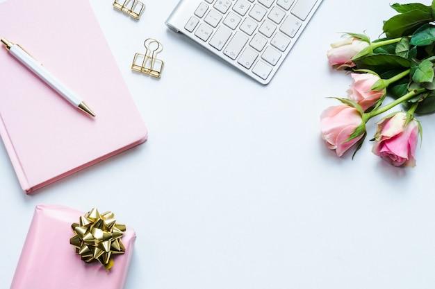 Cuaderno rosa, un bolígrafo, una caja de regalo, un teclado y rosas rosadas sobre un fondo blanco.
