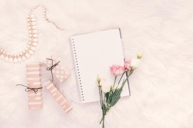 Cuaderno con rosas y cajas de regalo en manta.