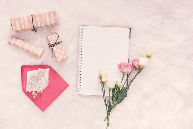 Cuaderno con rosas, regalos y sobre en manta.