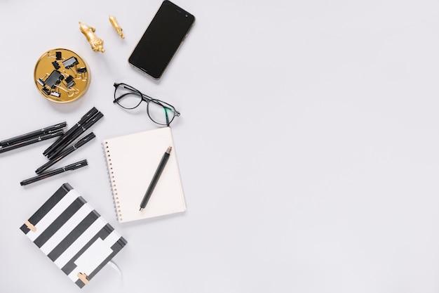 Cuaderno; rotulador; los anteojos; papelería y teléfono celular en el fondo blanco