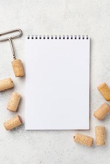 Cuaderno con sacacorchos y tapones de vino