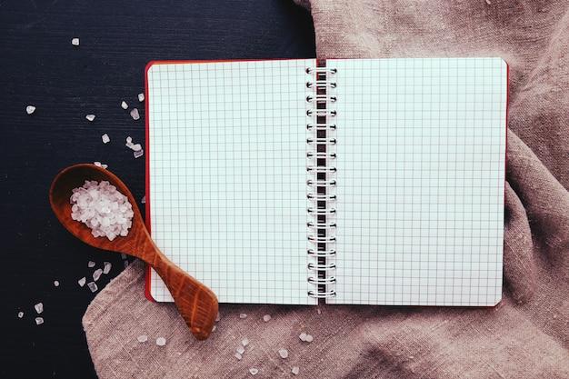 Cuaderno y sal marina en cuchara de madera