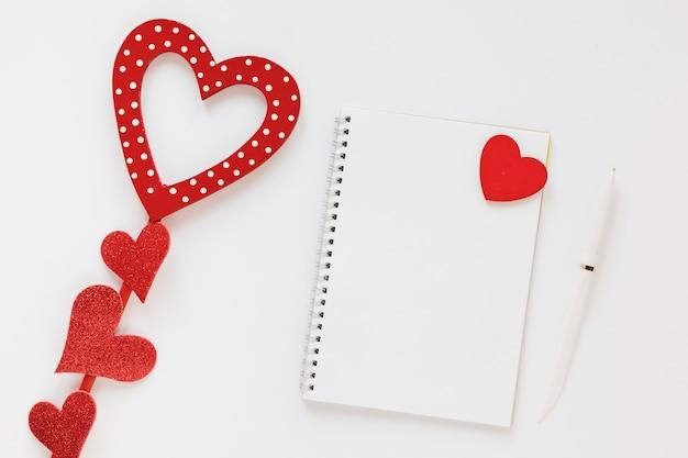 Cuaderno de san valentín con bolígrafo y corazones