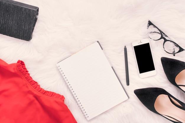 Cuaderno con smartphone y falda sobre manta.