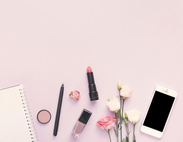Cuaderno con smartphone, flor y cosmética en mesa de luz.