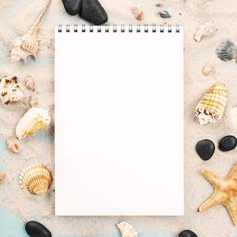 Cuaderno sobre arena con mariscos