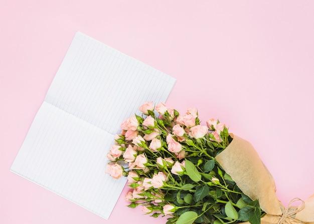 Cuaderno de una sola línea y ramo de rosas sobre fondo rosa.