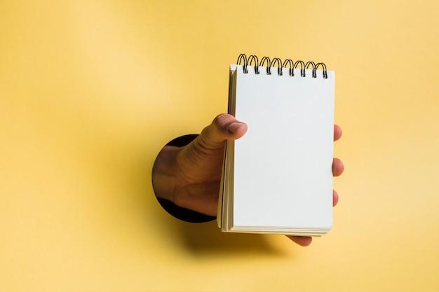 Cuaderno sostenido por persona con fondo amarillo.
