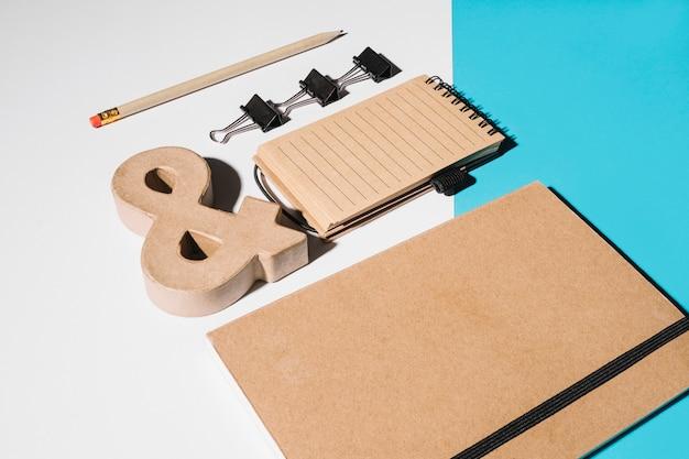 Cuaderno de tapa marrón cerrado con letrero de comercial; clips de bulldog y cuaderno de espiral