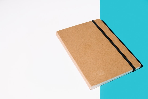 Cuaderno de tapa marrón sobre fondo blanco y azul