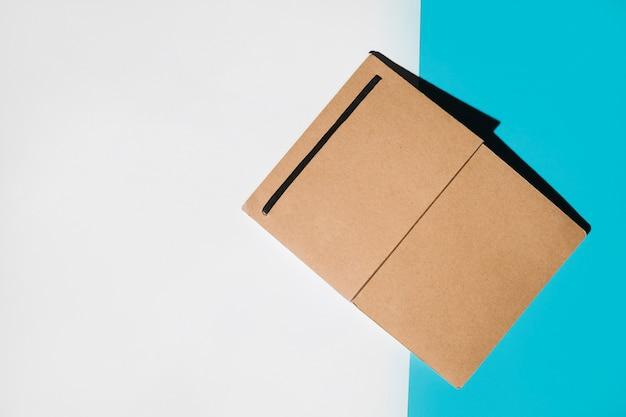 Cuaderno de tapa marrón solo sobre fondo blanco y azul.