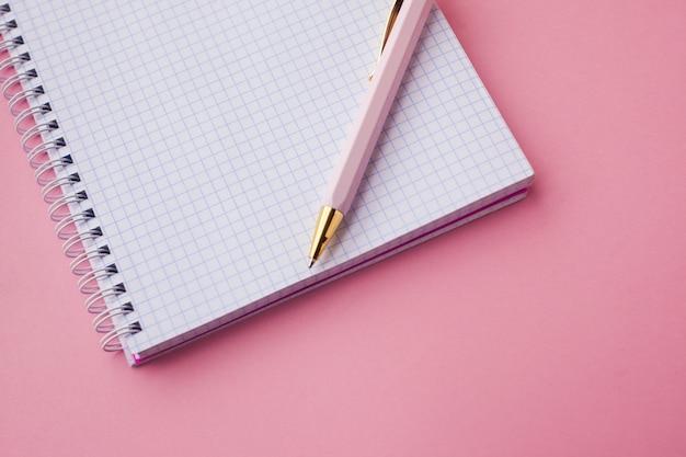 Cuaderno con tapa de plástico color rosa, bolígrafo y clips. fondo rosa enfoque selectivo