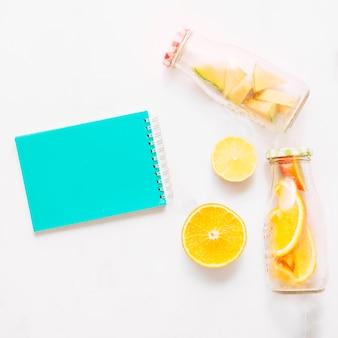 Cuaderno con tapa turquesa, lima naranja y botellas de vidrio con cítricos cortados.