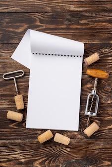 Cuaderno con tapones de vino y sacacorchos