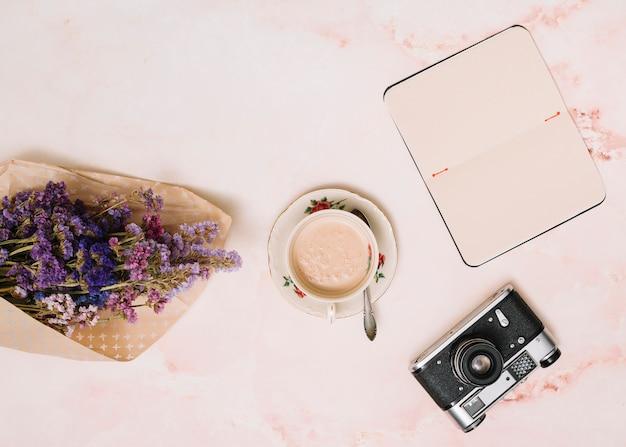 Cuaderno con taza de café, cámara y ramo de flores en mesa