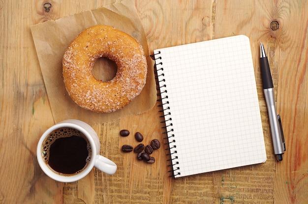 Cuaderno y taza de café con donut sobre fondo de madera vieja