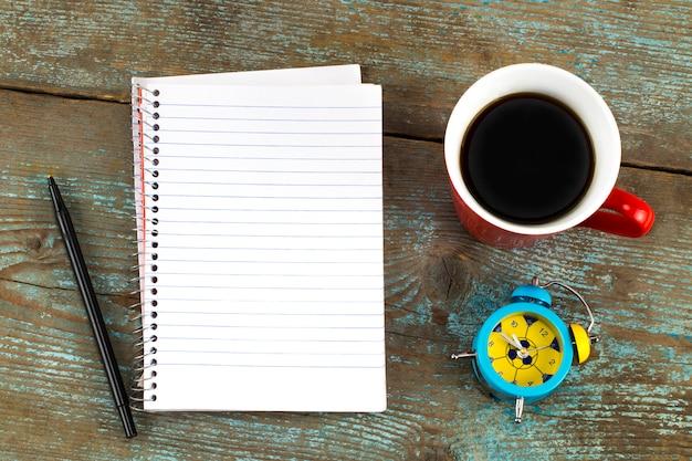 Cuaderno, taza de café en el escritorio de madera. vista superior