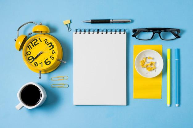 Cuaderno y taza de café plana.