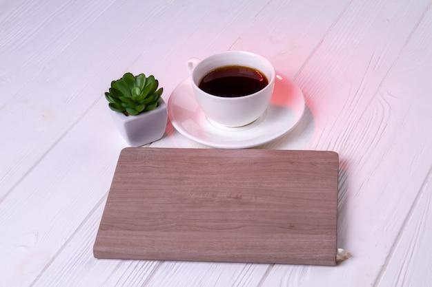 Cuaderno con taza de café y planta. fondo de escritorio blanco.