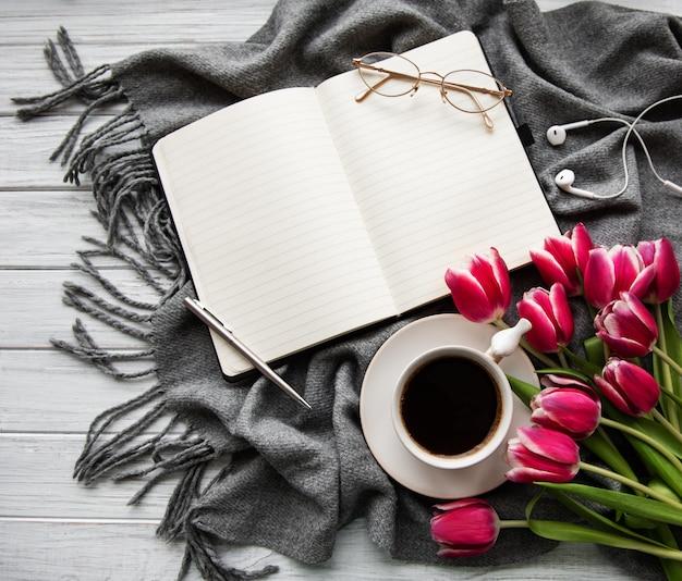Cuaderno, taza de café y tulipanes rosados.