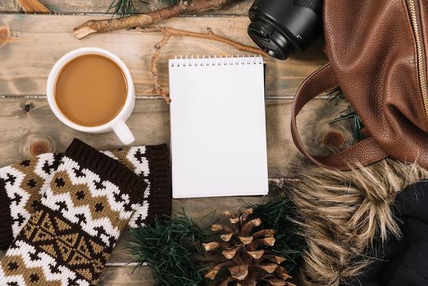 Cuaderno y taza cerca de bolso.