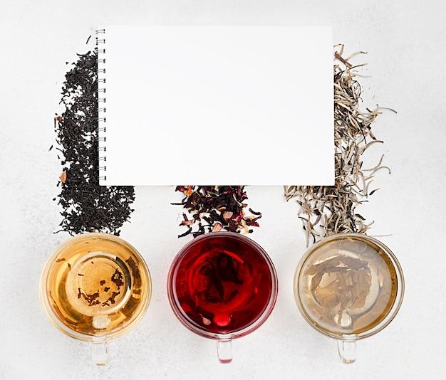 Cuaderno y tazas de té con hierbas naturales.