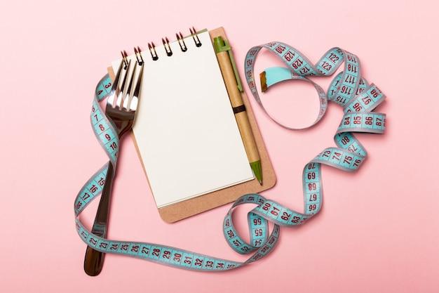 Cuaderno con tenedor y cinta métrica azul