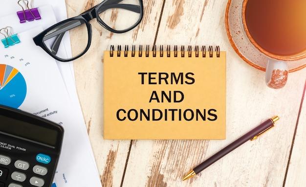 Cuaderno con términos y condiciones de texto sobre la mesa de oficina, documentos, calculadora, gafas y bolígrafo