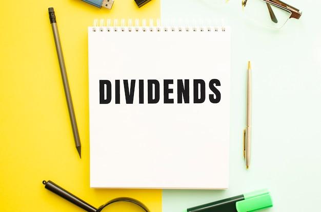 Cuaderno con texto dividendos en mesa de oficina con material de oficina