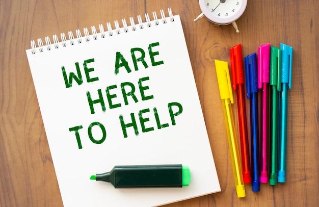 Un cuaderno con el texto estamos aquí para ayudar en una hoja blanca yace sobre una mesa de madera marrón con bolígrafos de colores. concepto de negocio.
