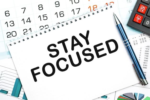 Cuaderno con el texto manténgase enfocado en la mesa de la oficina, documentos, calculadora, gafas y bolígrafo